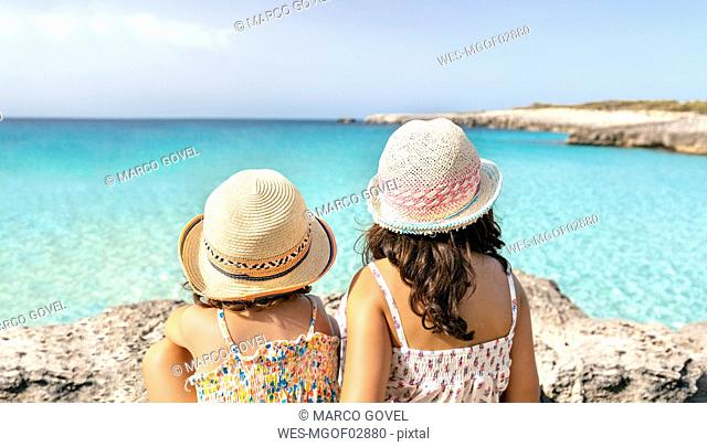 Girls sitting at the beach looking at the sea