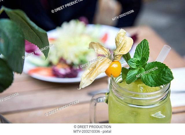 View of yellow mocktail in jar glass by bowl of salad