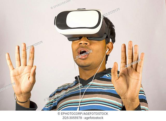 Scared young boy wearing virtual reality goggles and enjoying in scary 3D VR video