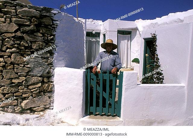 Man standing near a green portal and behind him, a white house , Sikinos, Cyclades, Greece