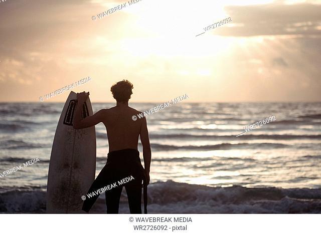 Man carrying surfboard standing on beach