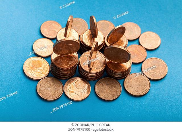 Euro cent coins in one cent and two cents denominations on blue background