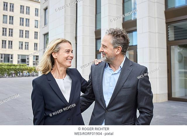 Smiling businessman and businesswoman in the city facing each other
