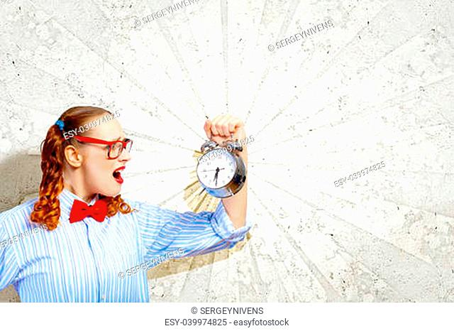 Young woman with an old-fashioned alarm clock