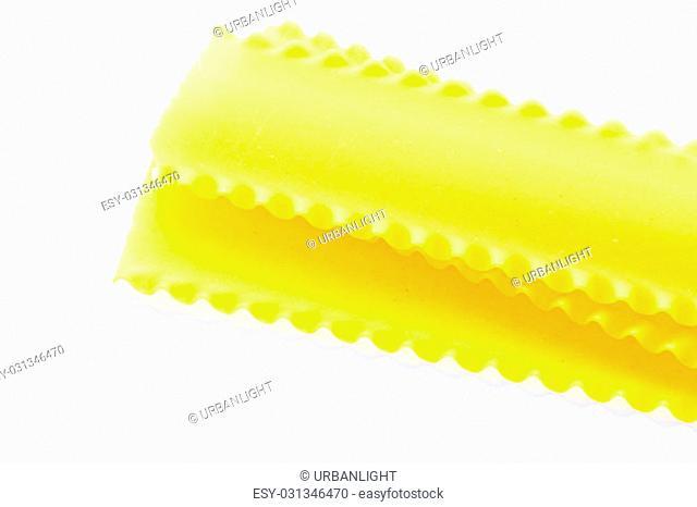 Organic yellow lasagne pasta on a white background