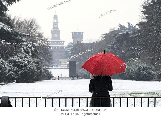 A woman with red umbrella admires the view of Sempione park during a snowfall. Milan, Lombardy, Italy, Europe