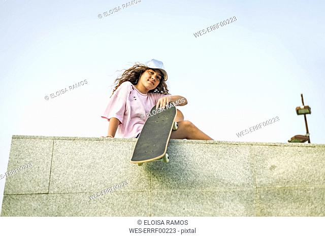 Girl with skateboard sitting on wall