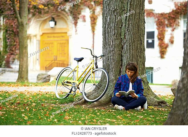 Girl reading book on university campus in fall with yellow bicycle; Kingston, Ontario, Canada