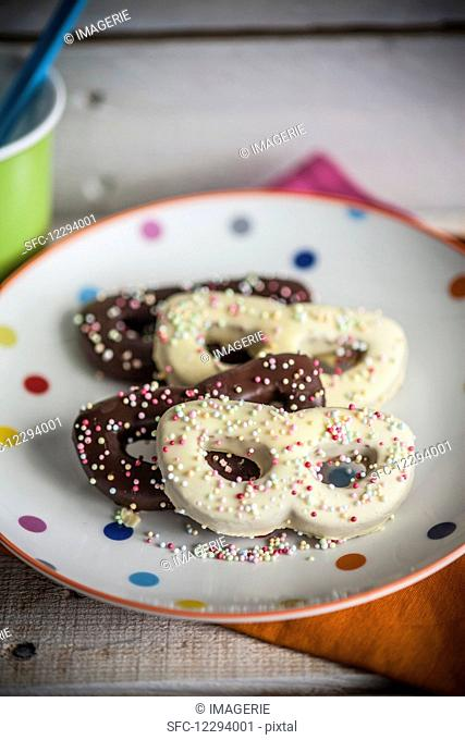 Sprinkle biscuits (carnival mask) with chocolate glazes and colourful sugar beads
