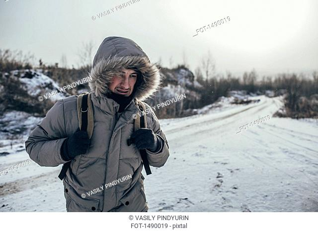 Hiker carrying backpack while standing on snow covered landscape