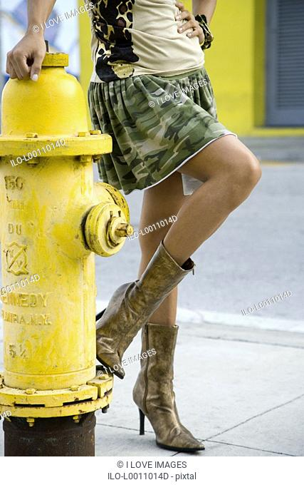 A young woman standing by a fire hydrant