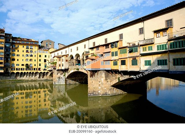 Ponte Vecchio medieval bridge across River Arno with view of merchants shops that line bridge and hang over the water below