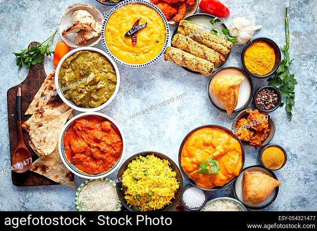Assorted indian food on stone background. Dishes of indian cuisine. Tikka masala, butter chicken, Nilgiri, seekh kebab, rice, Onion Bhajia, paneer, samosa, naan