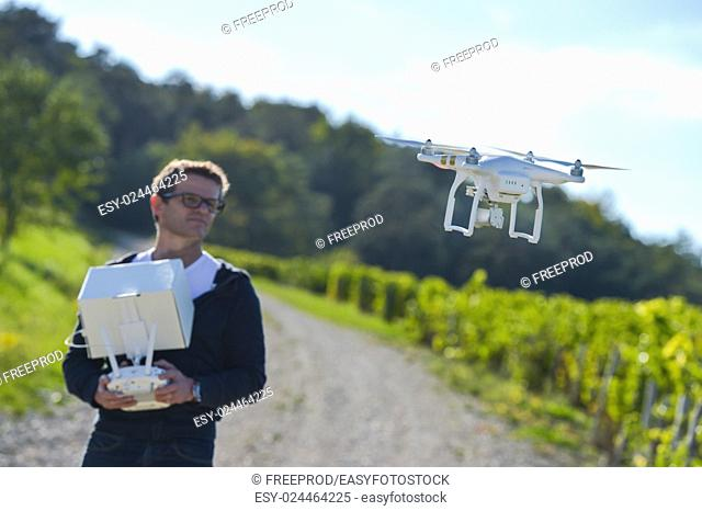 Man flying drone in wineyard, Champagne, France