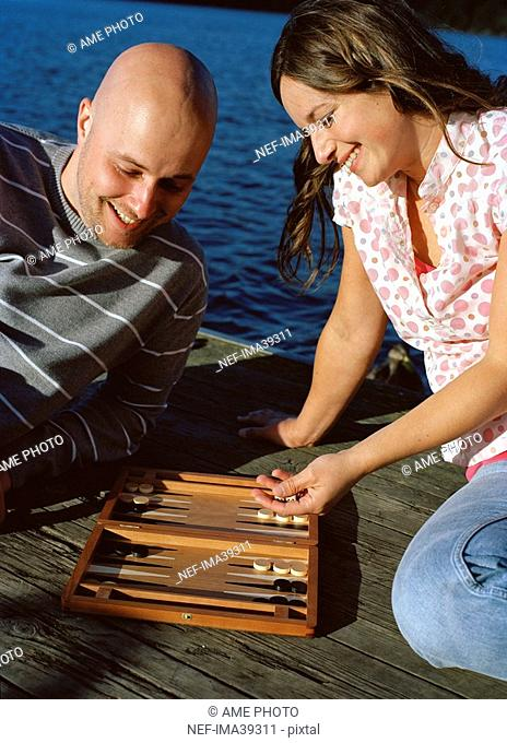 A man and a woman playing backgammon outside