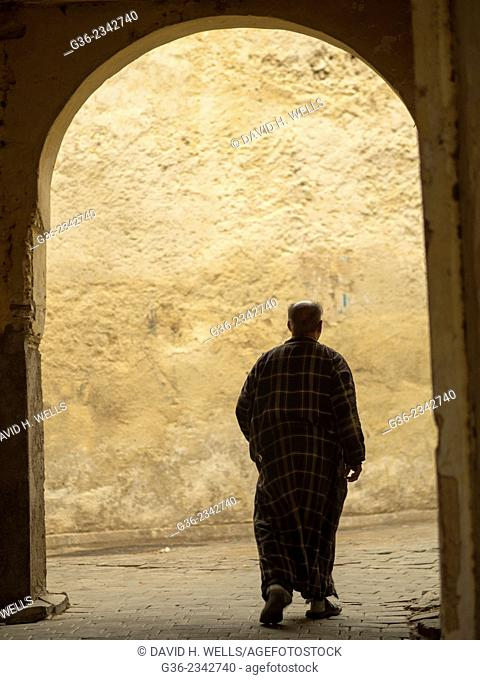 Silhouette of man walking through an archway in Fez, Morocco