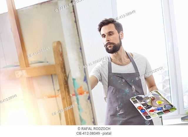 Male artist with palette painting at easel in art studio