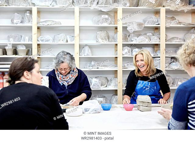 A group of four women chatting together and working on their pots in a pottery studio