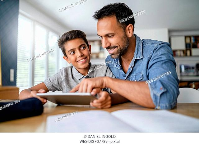 Father and son using tablet and doing homework