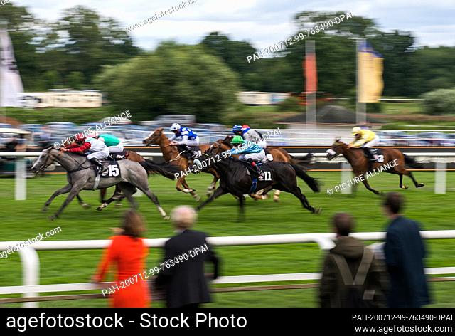 12 July 2020, Hamburg: Hamburg-Horn: horse racing: Gallop, Hamburg Derby: Jockeys gallop on their horses across the track in a race on day three of the 151st...