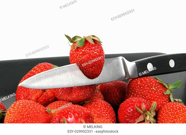 strawberries on Black Plate over White with knife
