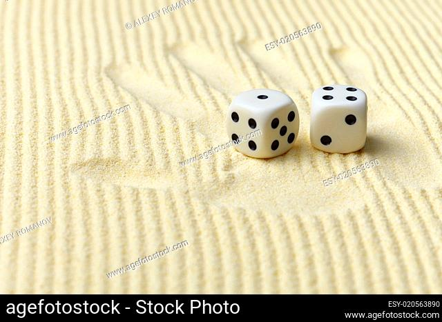 Dices on sand surface and palm print - art composition