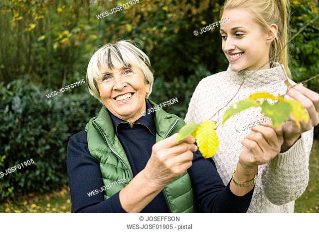 Happy young woman with her grandmother holding twig in garden