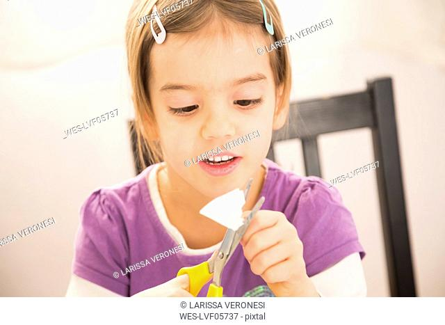 Little girl tinlering at home, cutting paper