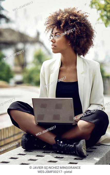Fashionable young woman with curly hair sitting on bench with laptop