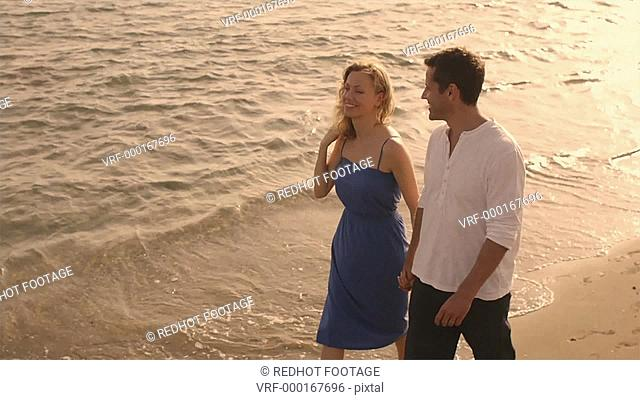 High angle shot of couple walking on beach, Marbella region, Spain