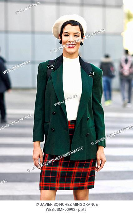 Portrait of smiling fashionable young woman on zebra crossing