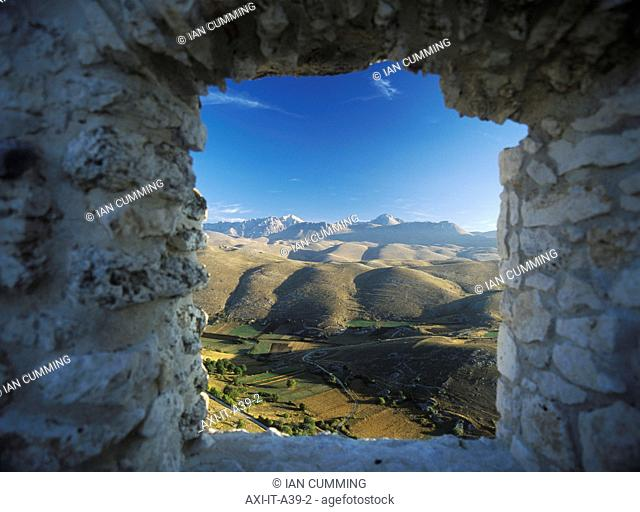 Looking out from old window in ruins of buildings beside Rocca Calascio to the Campo Imperatore and Parco Nazionale Gran Sasso at dawn, Abruzzo, Italy