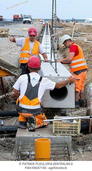 Workers put in a slotted gutter for draining the runway at Schoenefeld Airport inSchoenefeld,Germany, 08 June 2015. Renovation efforts have been underway for...