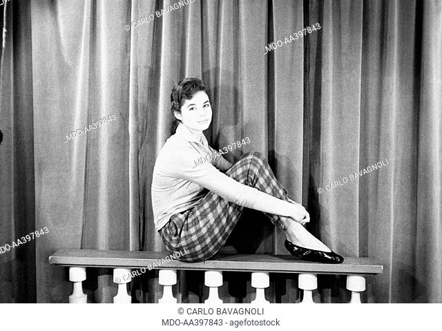 Giorgia Moll sitting on a parapet. Italian singer and actress Giorgia Moll sitting on a parapet and keeping her arms on her knees. December 1955
