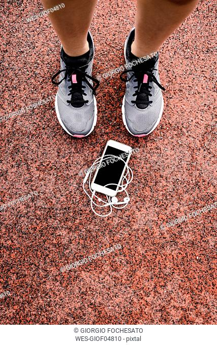 Lags of a teenage runner with smartphone and earphones lying on ground