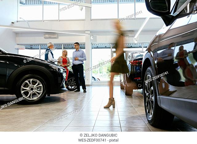 Car dealer advising customers with woman walking in foreground