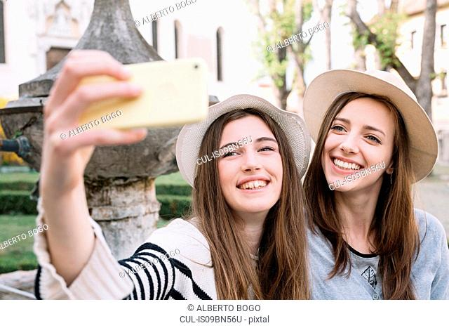 Girlfriends taking selfie at piazza, Belluno, Veneto, Italy