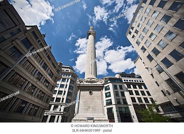 Monument on city street against blue sky