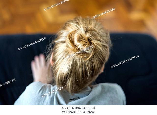 Woman with ginger hair bun sitting on sofa