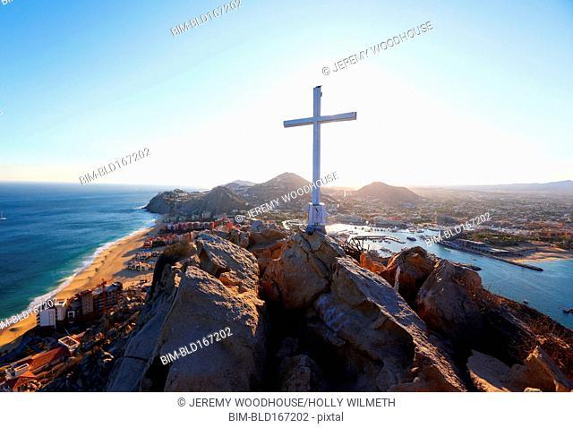 Cross on rocky mountaintop over Cabo San Lucas cityscape, Los Cabos, Mexico