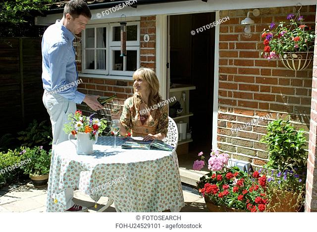 Couple enjoying wine at table in cottage courtyard setting&#10