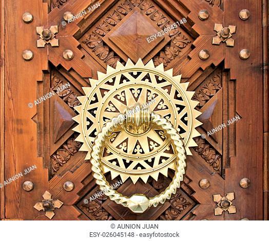 Luxury Golden doorknocker over carved wooden door