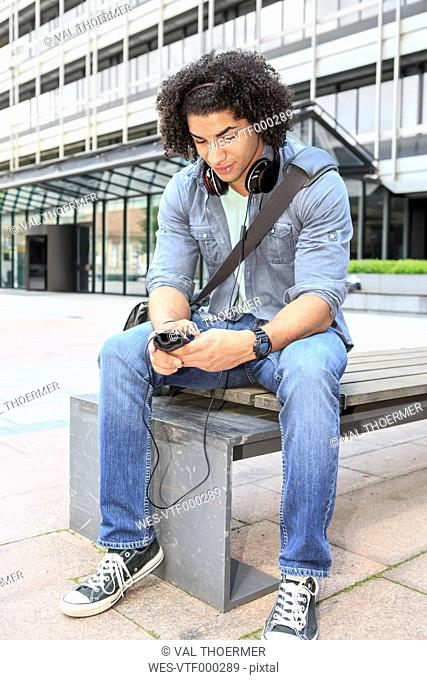 Young male student sitting on bench using his smartphone
