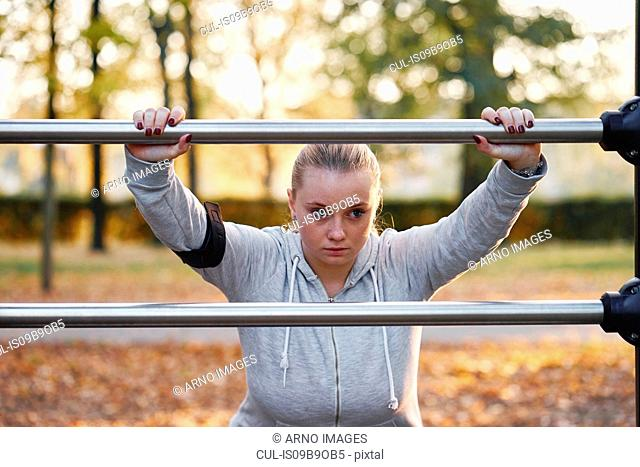 Curvaceous young woman training, leaning against handrail in park