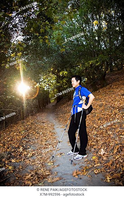 The early morning sun peaks through the trees as a male Korean hiker takes a break in a tree covered area of the Peak Trail at Mission Peak Regional Preserve in...