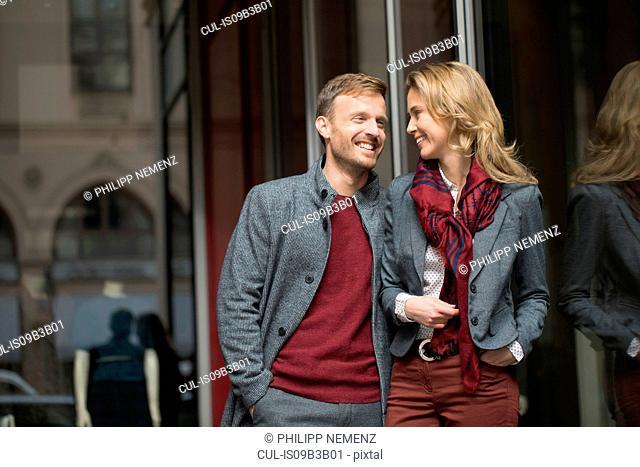 Mid adult couple strolling on city street