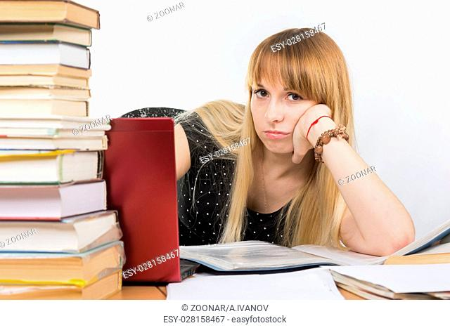 Girl student sitting at a desk with a laptop and sadly looks out from behind a pile of books
