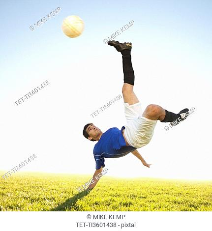Soccer player jump kicking