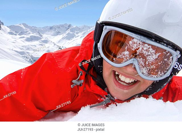 Close up of boy in helmet and goggles laying in snow