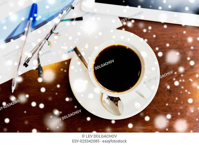 business and drinks concept - coffee cup, charts and tablet pc on table over snow